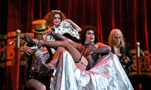 Tim Curry as Dr. Frank N. Furter along with his crew of strange assistants